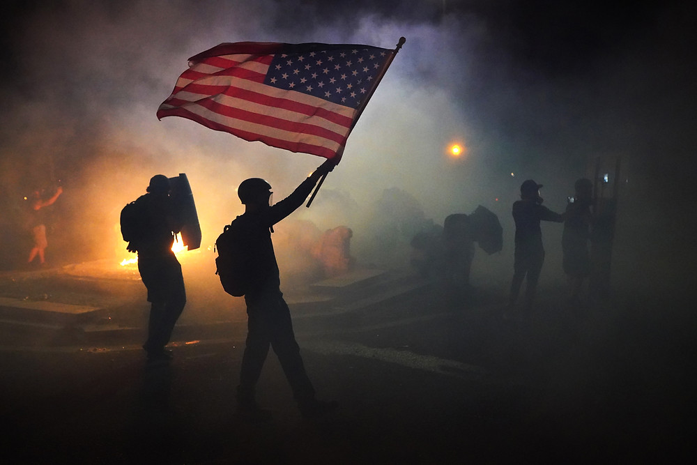Federal officers holding an American flag in a smoke filled, dark street