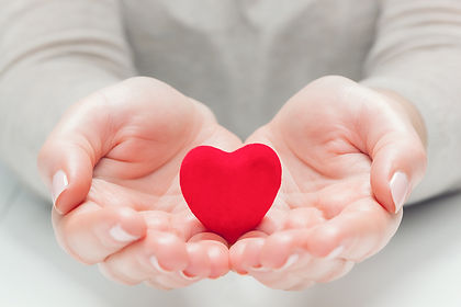 small-red-heart-in-womans-hands-in-a-ges