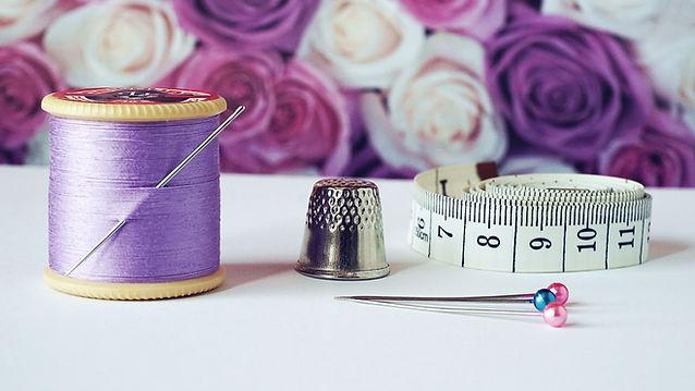 spool-of-purple-thread-near-needle-thimb