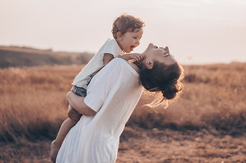 Young woman kisses her little son at sun