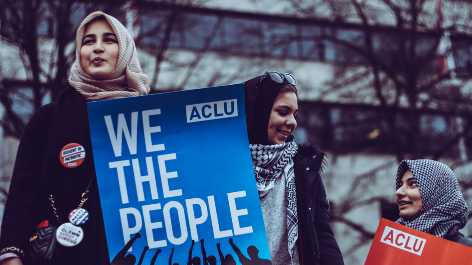 "4. Three women in hijab, one holding ""We the People"" sign"