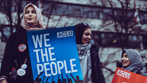 """4. Three women in hijab, one holding """"We the People"""" sign"""