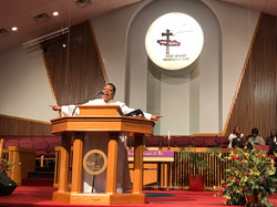 Pastor Chris Preaching with arms wide at