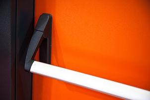 Emergency exit door. Closed up latch and orange door handle of emergency exit. Push bar an