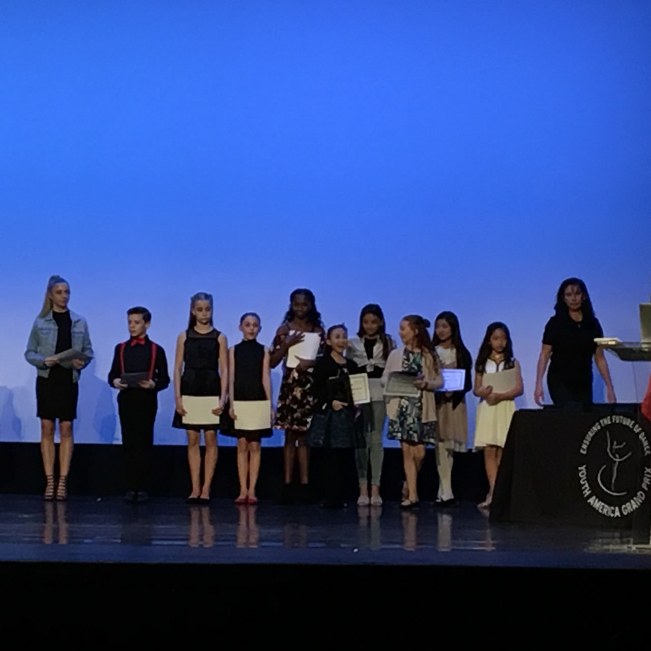 Our little ones on stage receiving awards with Karina Plantadit.