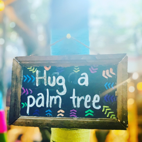 Hug a palm tree sign.