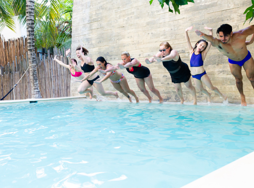 A group of people jumping into the pool at Zorba Tulum