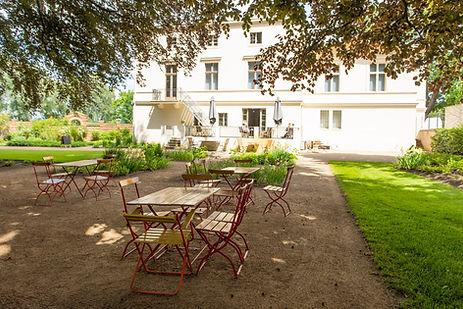 Außenansicht Terassenbereich Villa Schöningen mit Bestuhlung vom Café