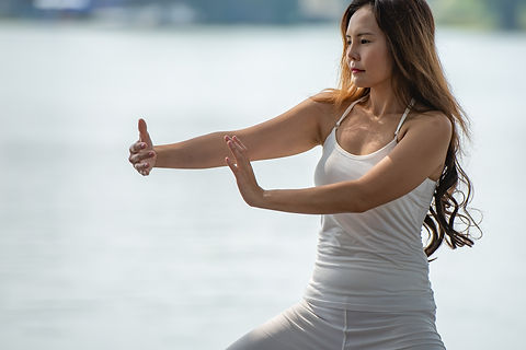 Young woman doing traditional Tai Chi Ch