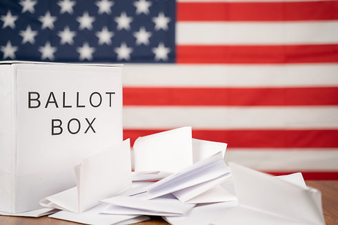 Ballot Box with votes on table before counting with US flag as background concept of Ballo