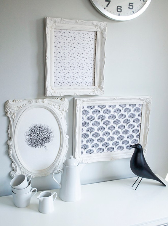 white picture frames with white crockery and an ornamental blackbird