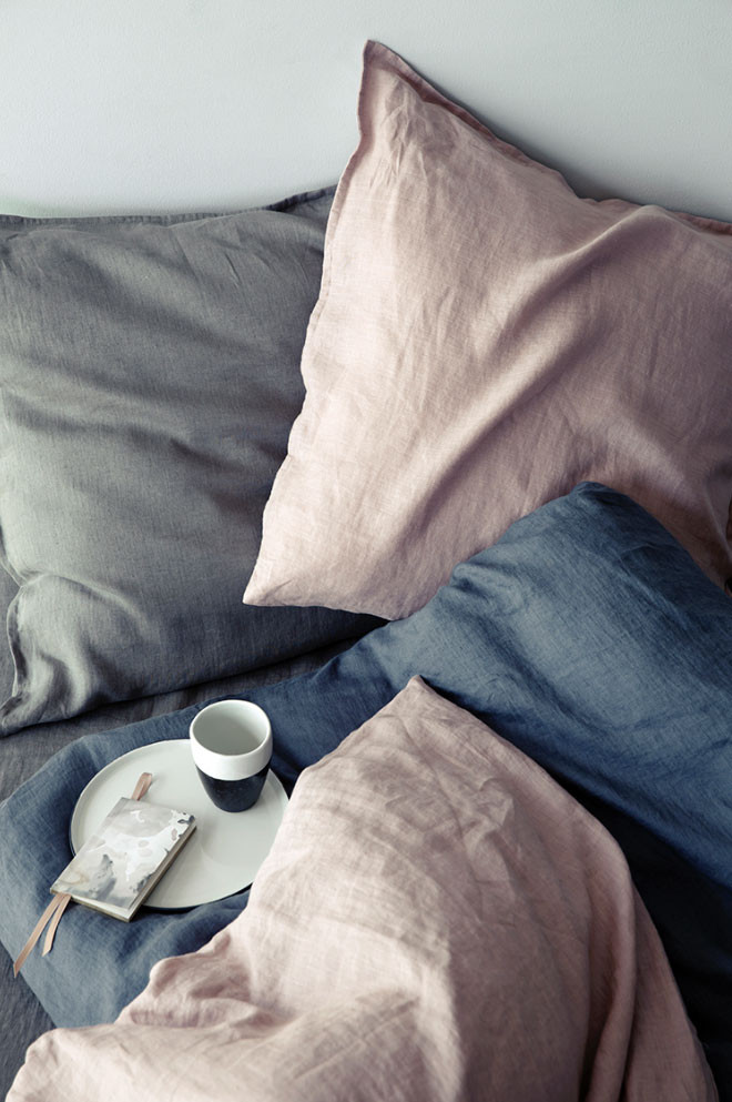 Linen bedding with mug of tea on bed
