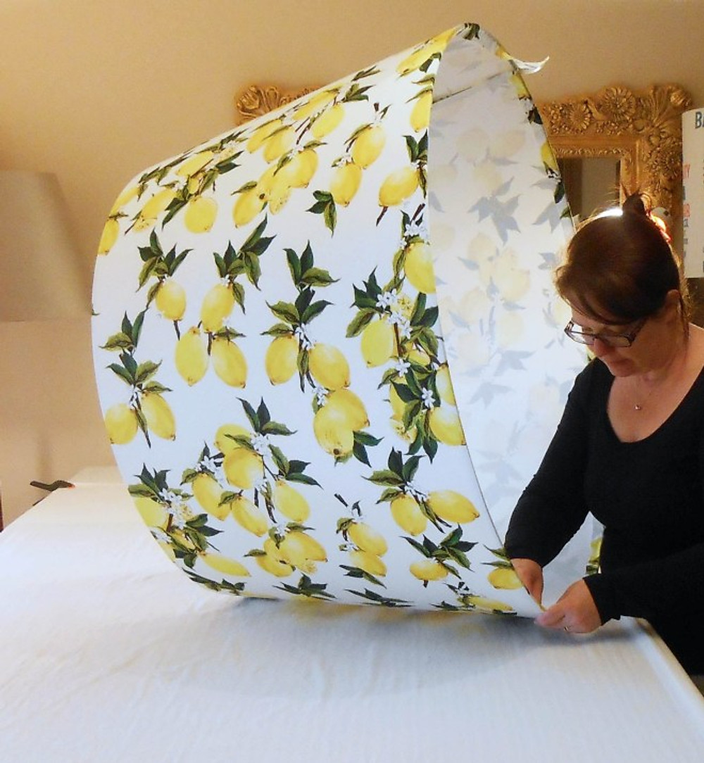 Lampshade maker making a huge, 1meter lampshade covered in fabric with a lemon print