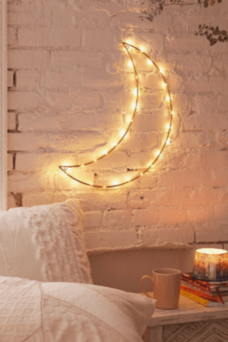 Fairy lights in the shape of a moon, hung on a white wall
