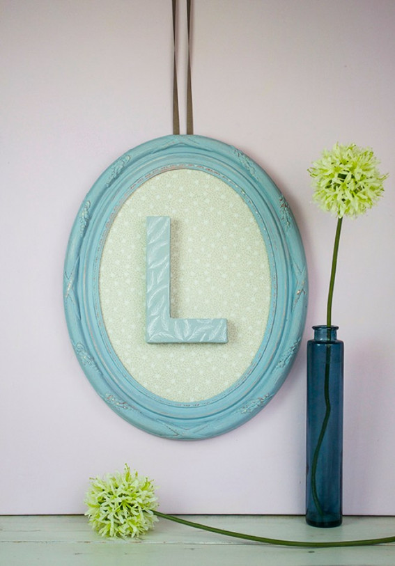 Oval picture frame on wall with letter L in centre and yellow flower to side