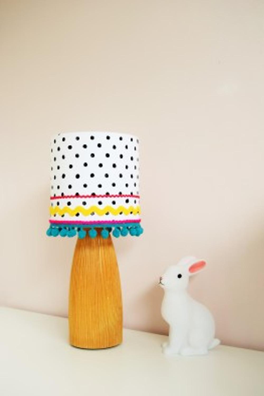 Handmade drum lampshade with polka-dot fabric and pom pom trim.