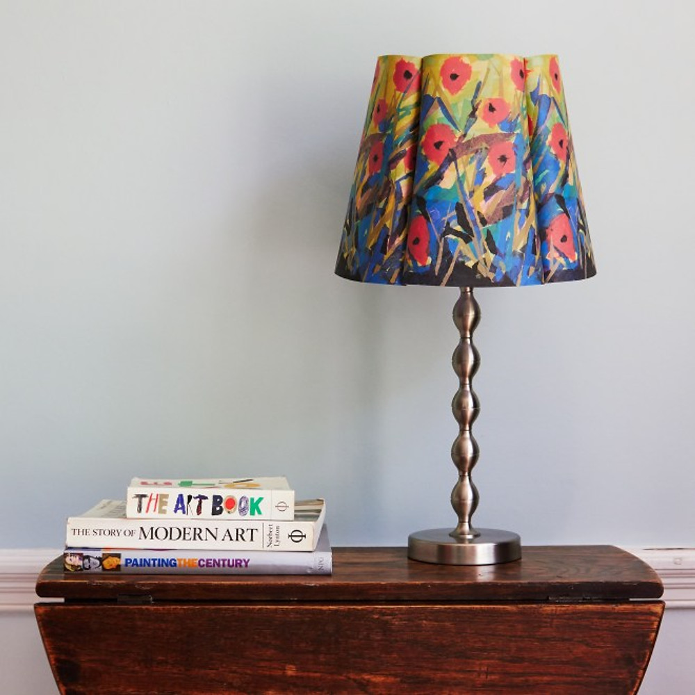 Table with Papershade lampshade and pile of books