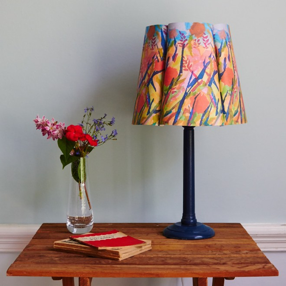 Lifestyle scene of a table with a Papershades lampshade and a vase of flowers