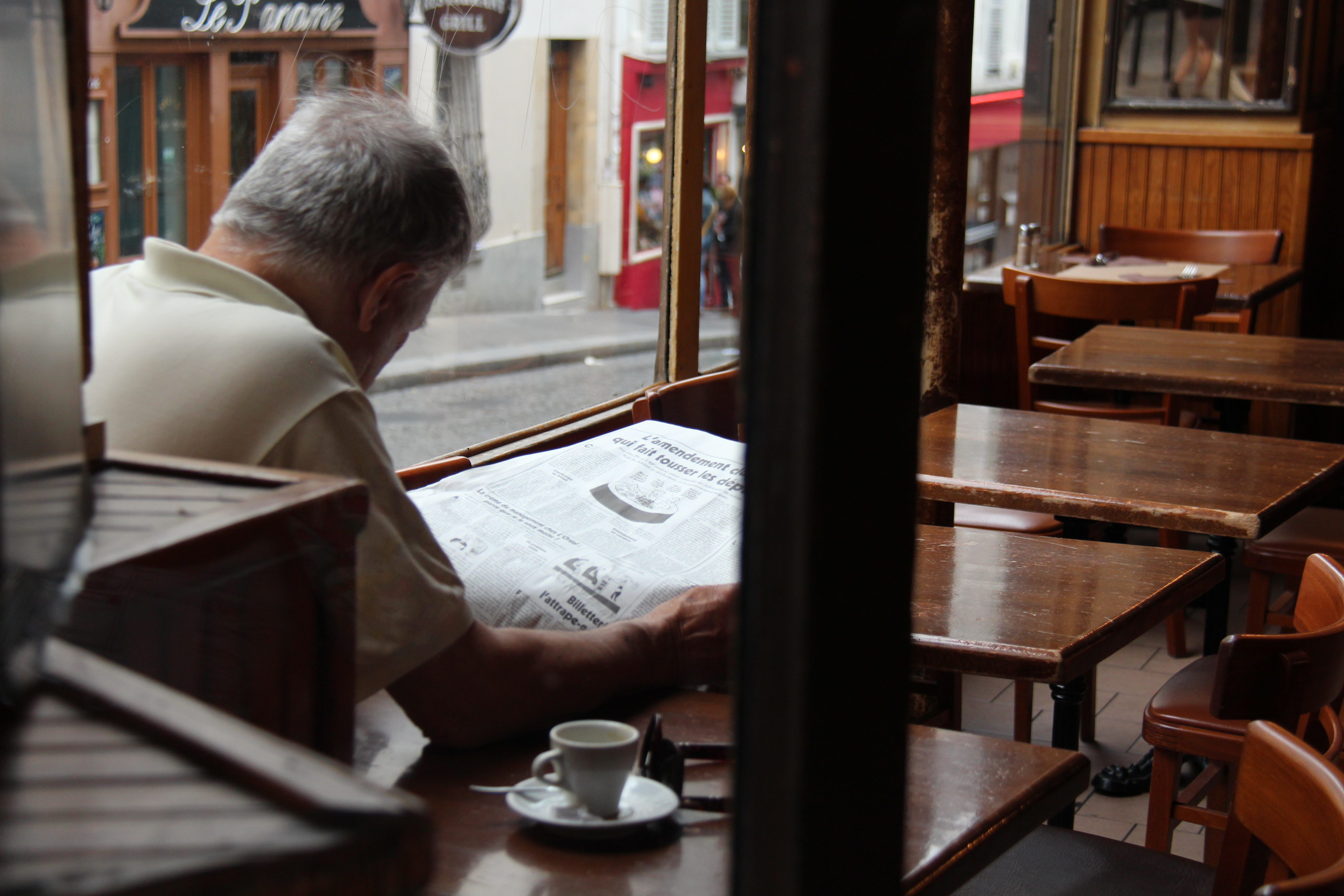 Man reading the newspaper at a cafe in Paris, France