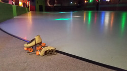 A pair of skates by the rink floor.