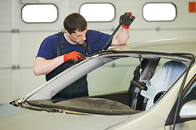 Auto technician replacing windshield