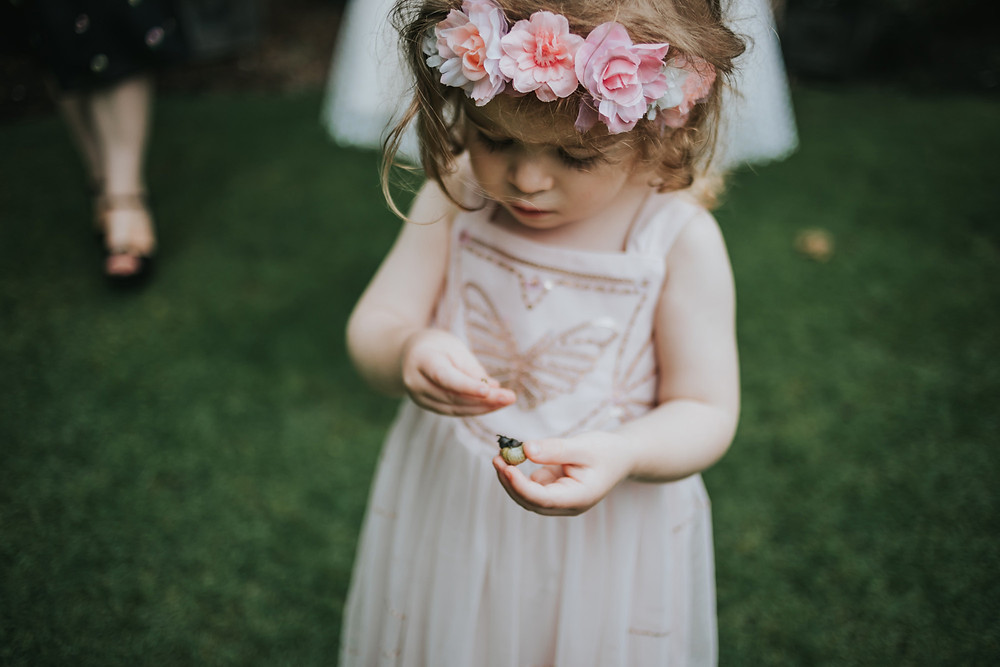 flower girl holding a snail in the gardens at holdsworth house