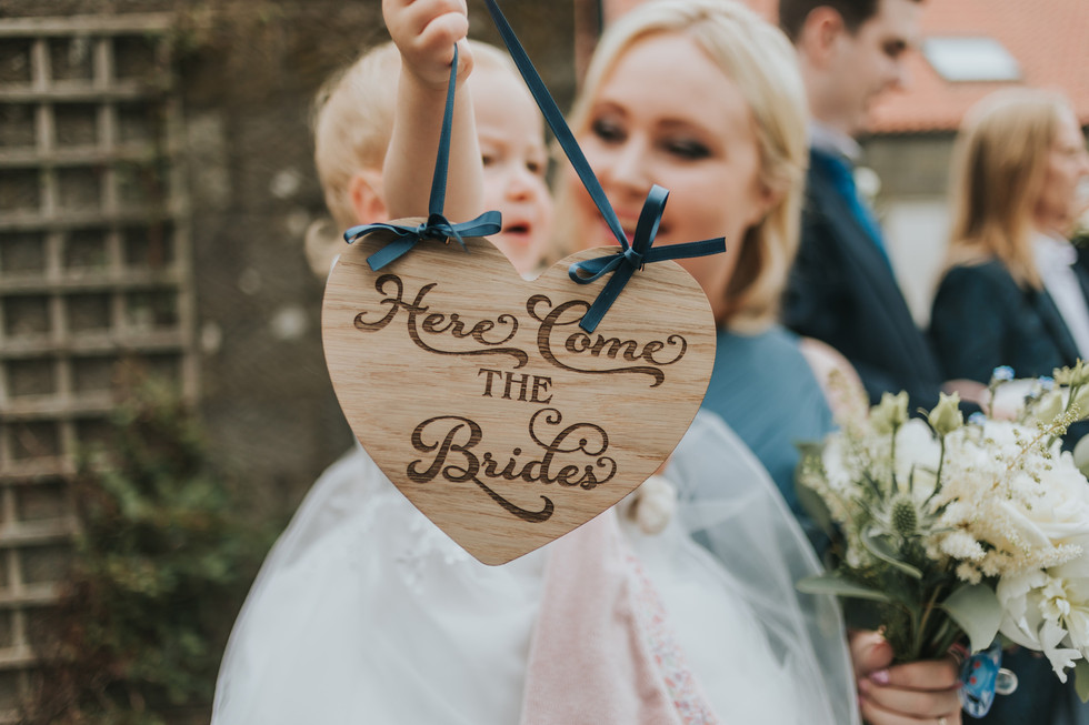toddler flower girl holding a wooden sign that reads 'here come the brides'
