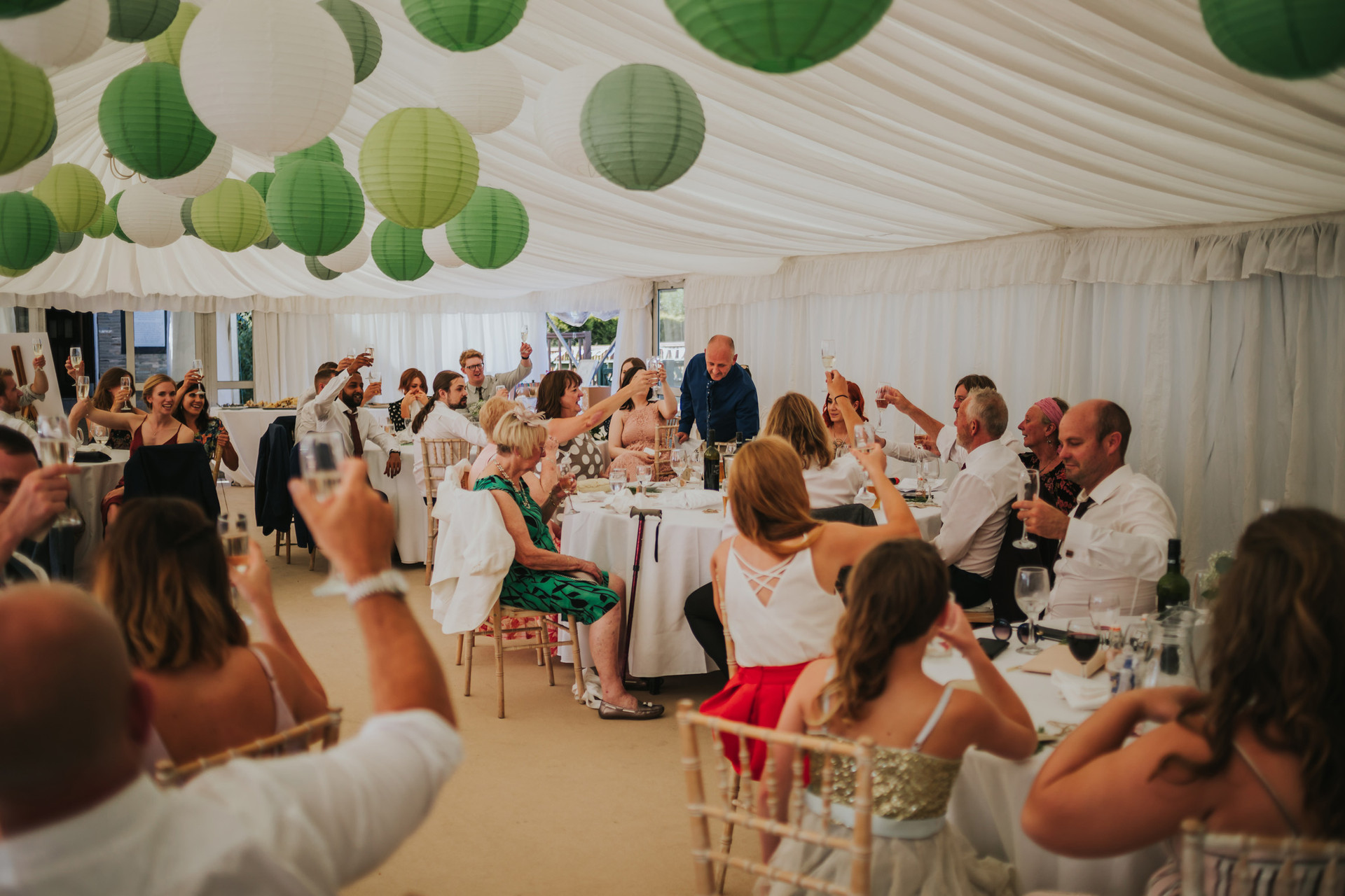 all the guests in the wedding marquee toasting the bride and groom