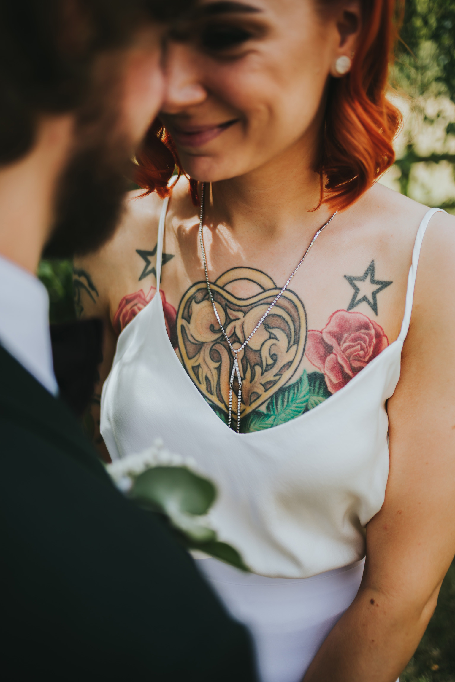 bride with a chest tattoo on show through her dress smiling at the groom