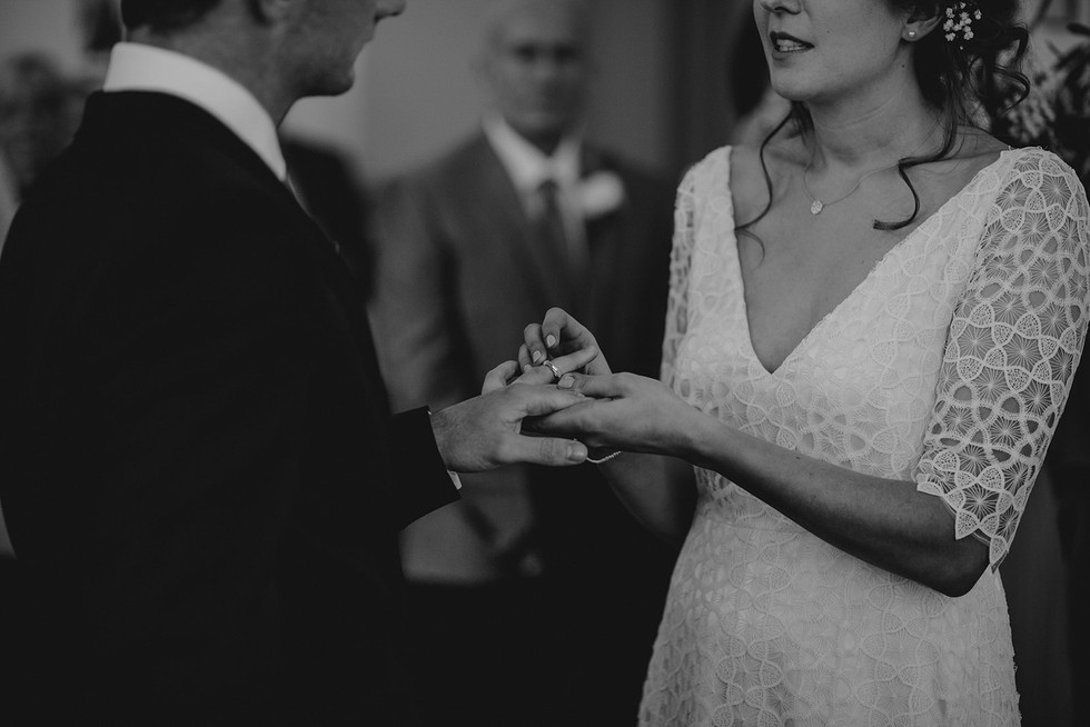 bride putting wedding ring on the grooms finger