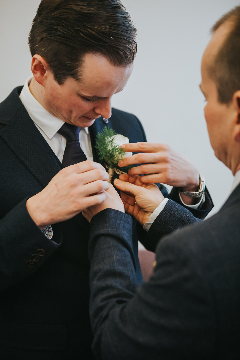 Groom putting on a corsage in leeds town hall