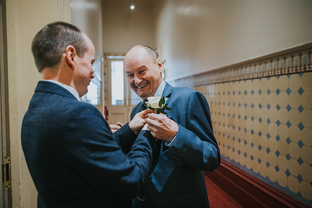 dad laughing having his corsage put on