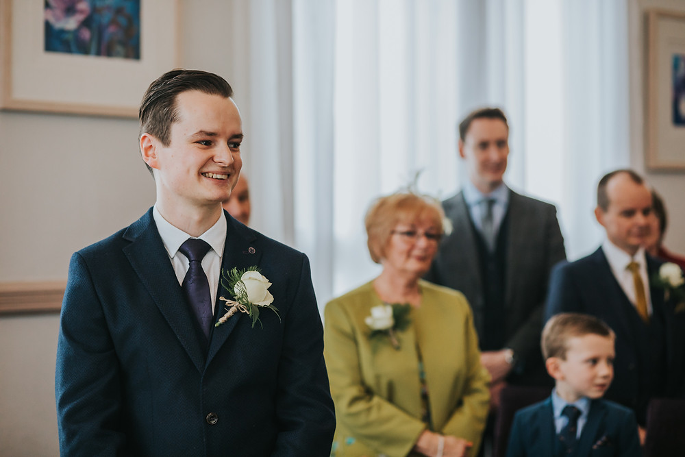 groom smiling at the brides entrance at leeds town hall wedding ceremony