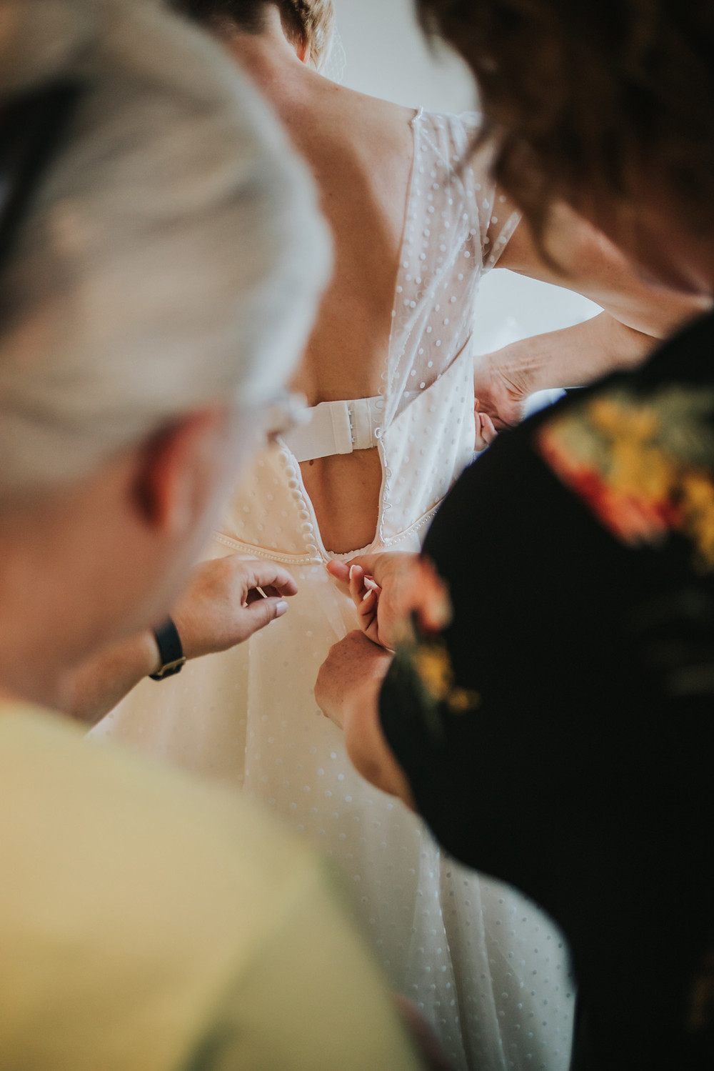 Bride putting on her wedding dress with help from her friends