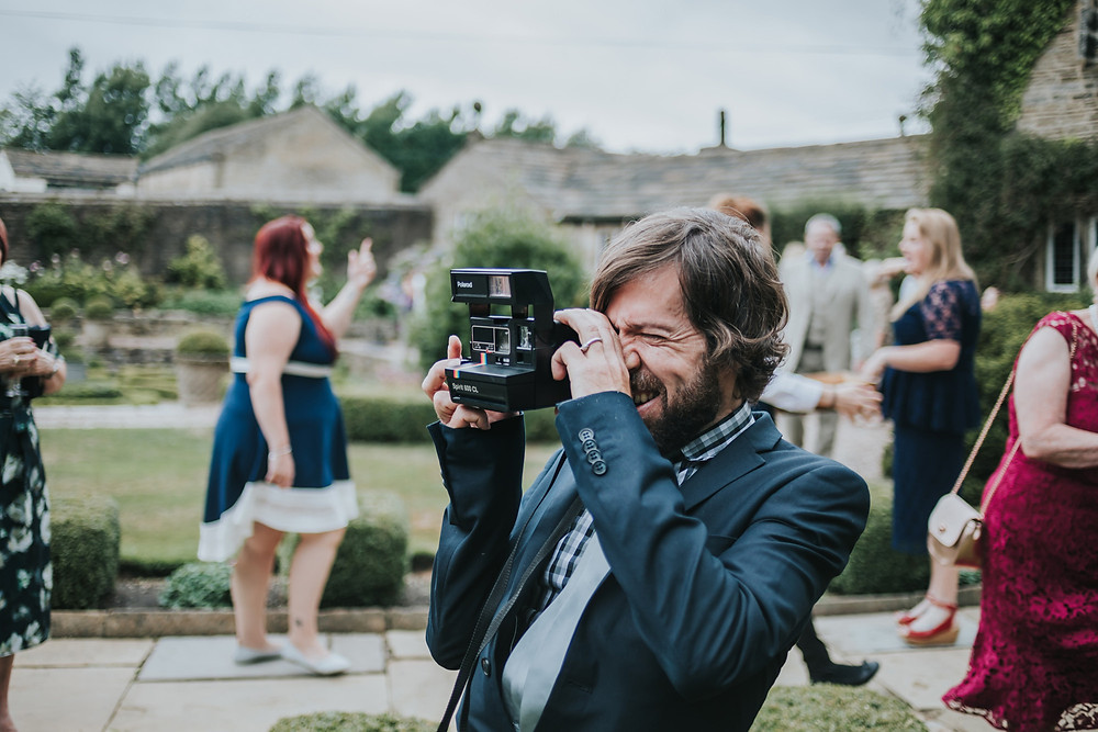 guest taking a photo on a retro polaroid camera outside the venue