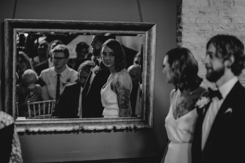 bride looking in a mirror during the ceremony at the old white beare