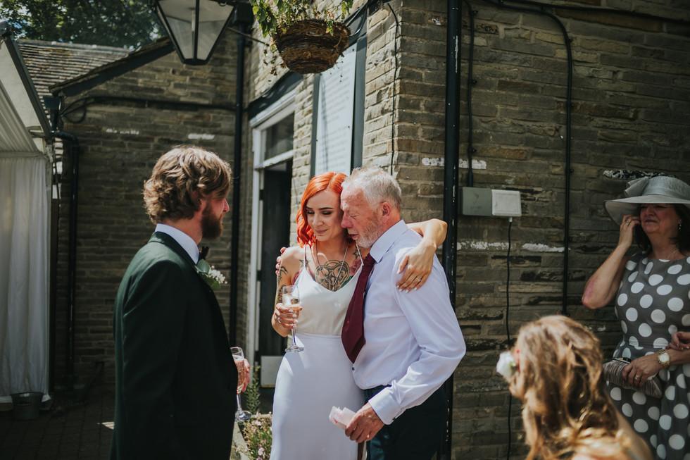 tatooed bride hugging her dad