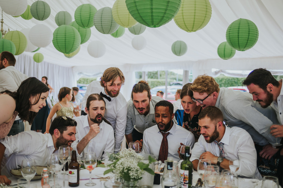 Guests gathered around a table watching the football on a phone