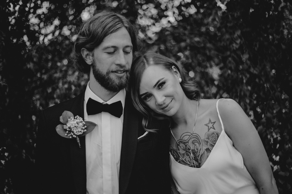 tattooed bride resting her head on the grooms shoulder