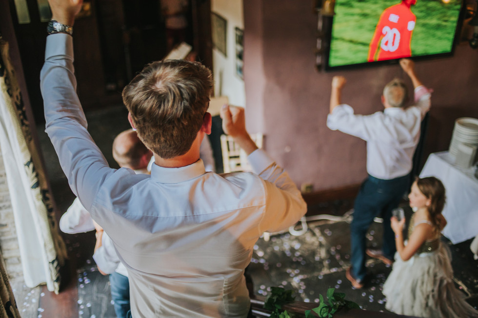 guests cheering watching england playing football on a tv in the snug