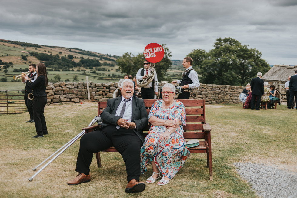 guests relaxing outside on a bench watching a brass band at Danby Castle