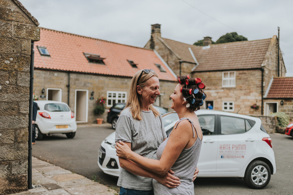 two brides at bridal prep outside a cottage