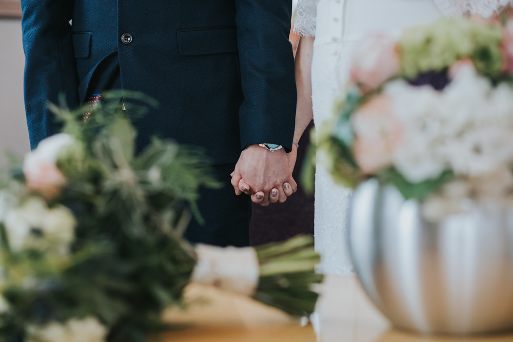 couple holding hands exchanging wedding vows