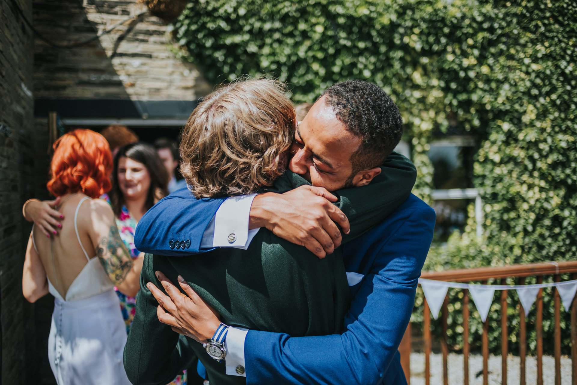 groom hugging his friend in the pub garden