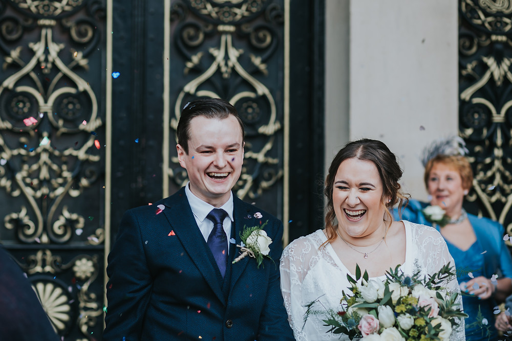 couple laughing under confetti at the town hall