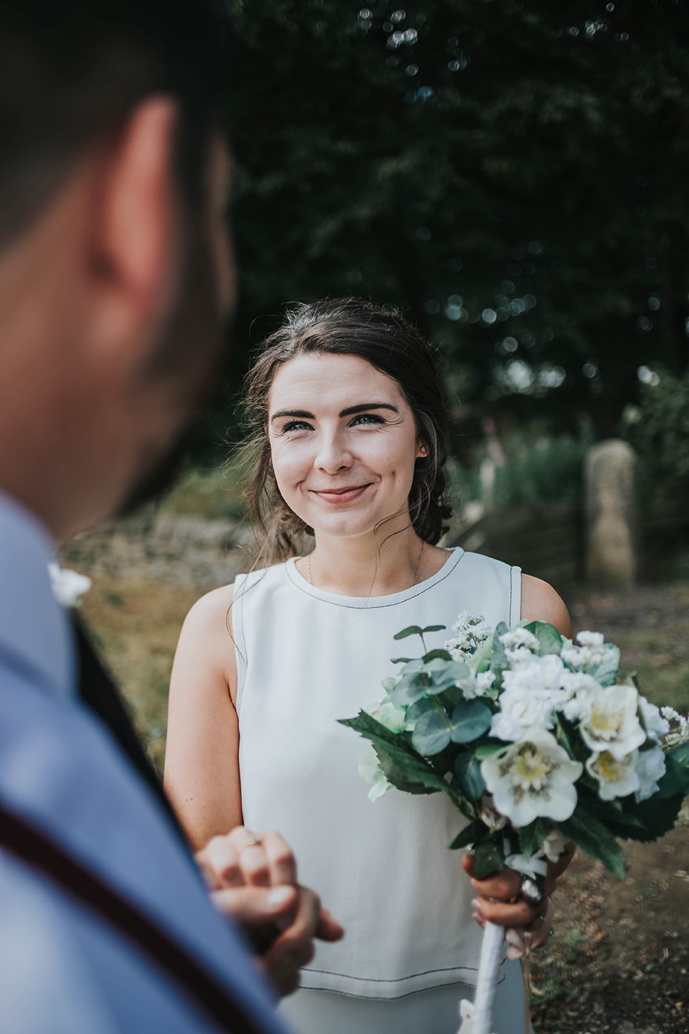 bride holding her bouquet and looking at the groom