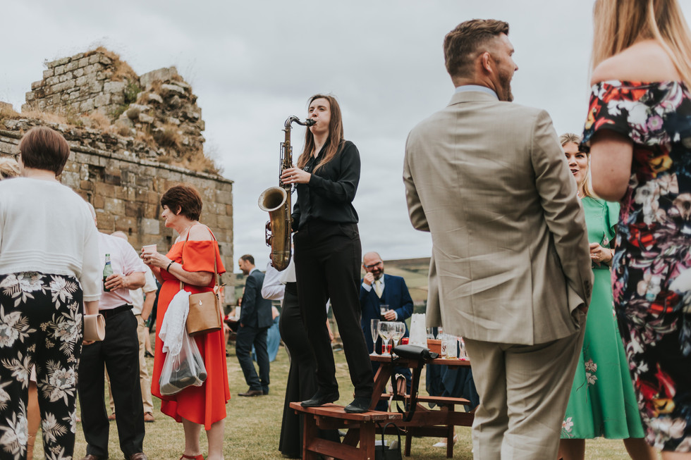 wedding saxaphone player stood on a table at Danby Castle