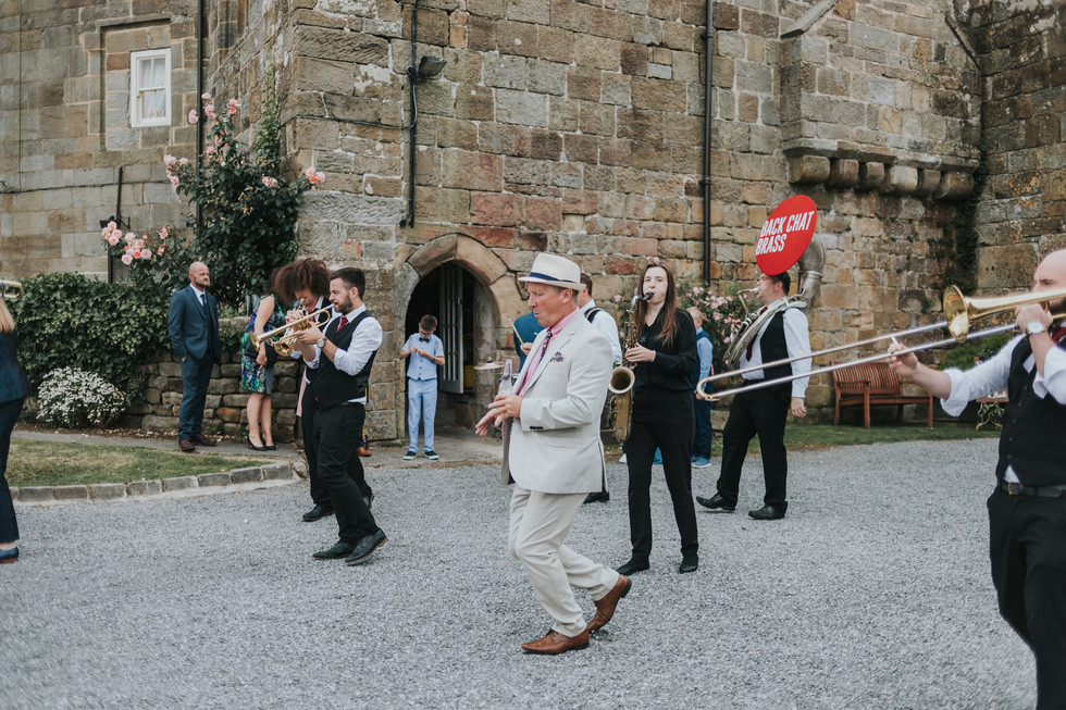 wedding guest dancing to a brass band