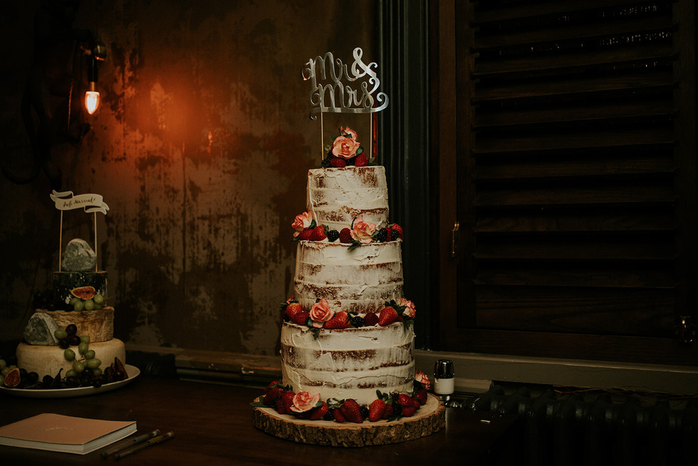 naked wedding cake covered in fruit and flowers