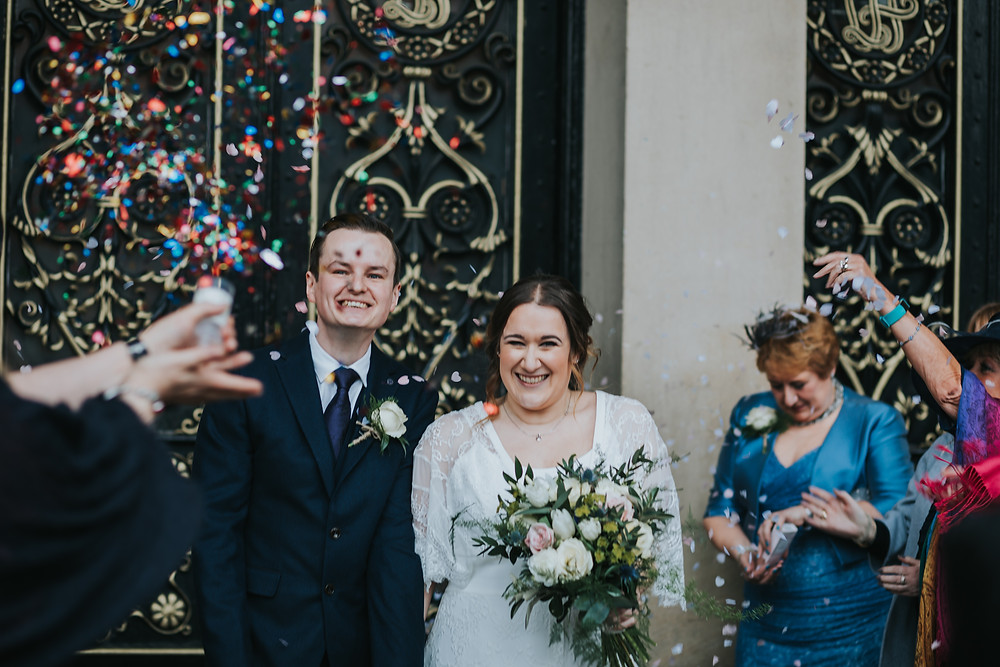 guests throwing confetti at leeds town hall wedding